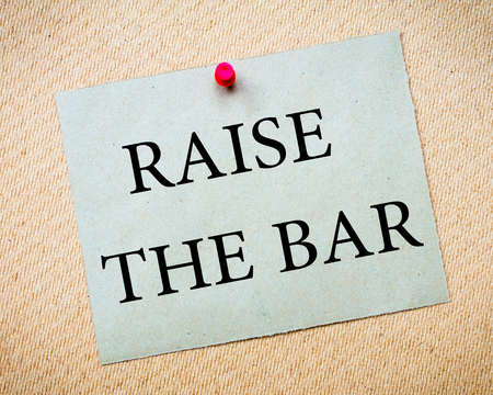 idioms: Raise The Bar Message. Recycled paper note pinned on cork board. Concept Image Stock Photo