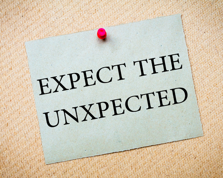 unpredictable: Expect the Unexpected Message. Recycled paper note pinned on cork board. Concept Image Stock Photo