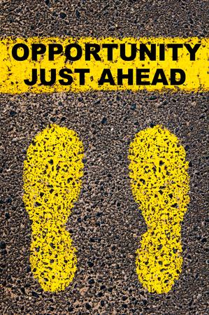 just ahead: Opportunity Just Ahead message. Conceptual image with yellow paint footsteps on the road in front of horizontal line over asphalt stone background. Stock Photo