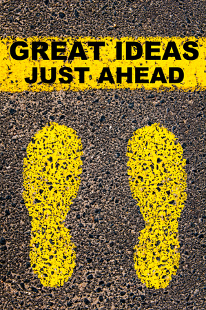 just ahead: Great Ideas Just Ahead message. Conceptual image with yellow paint footsteps on the road in front of horizontal line over asphalt stone background.