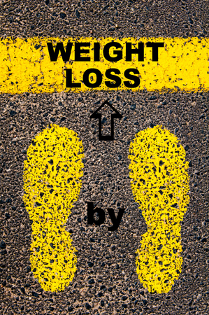 over weight: Weight Loss Step by Step message. Conceptual image with yellow paint footsteps on the road in front of horizontal line over asphalt stone background.