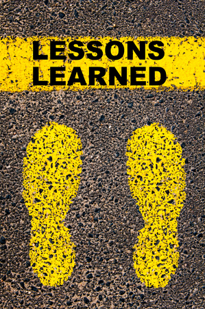 learned: Lessons Learned  message. Conceptual image with yellow paint footsteps on the road in front of horizontal line over asphalt stone background.