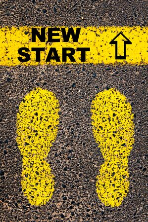yellow paint: New Start message. Conceptual image with yellow paint footsteps on the road in front of horizontal line over asphalt stone background. Stock Photo