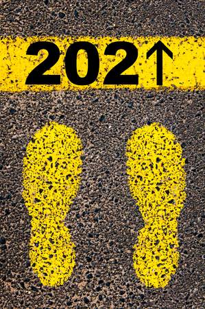 replaced: Year 2021 is coming message, number 1 replaced with arrow pointing forward. Conceptual image with yellow paint footsteps on the road in front of horizontal line over asphalt stone background.