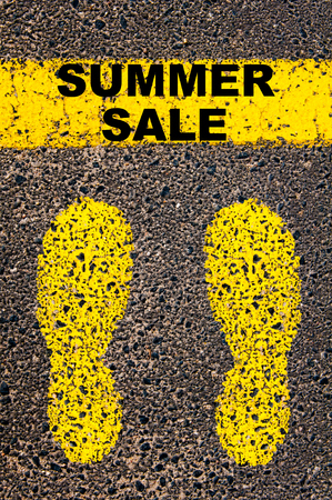 Summer Sale message. Conceptual image with yellow paint footsteps on the road in front of horizontal line over asphalt stone background.