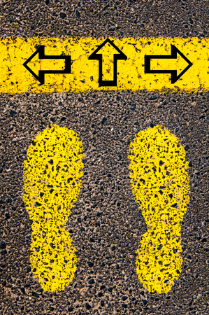 indecision: Arrows left, right, forward. Indecision Conceptual image with yellow paint footsteps on the road in front of horizontal line over asphalt stone background.