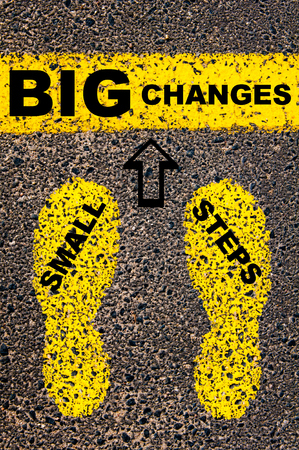 big and small: Small Steps Big Changes Message. Conceptual image with yellow paint footsteps on the road in front of horizontal line over asphalt stone background.