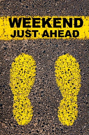 just ahead: Conceptual image with yellow paint footsteps on the road in front of horizontal line over asphalt stone background. Message Weekend Just Ahead.