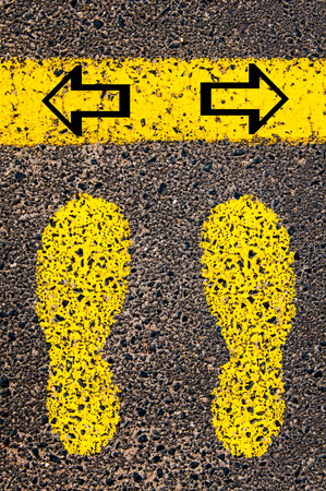 indecision: Arrows left and right. Indecision Conceptual image with yellow paint footsteps on the road in front of horizontal line over asphalt stone background.