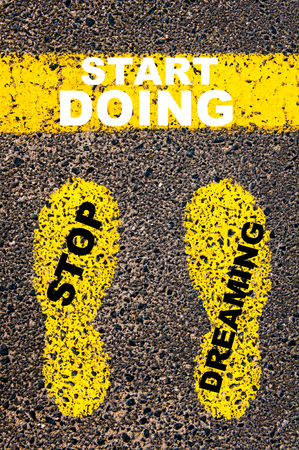 conceptual image: Stop Dreaming Start Doing Message. Conceptual image with yellow paint footsteps on the road in front of horizontal line over asphalt stone background.