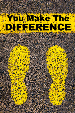 superiority: You Make the Difference message. Conceptual image with yellow paint footsteps on the road in front of horizontal line over asphalt stone background.