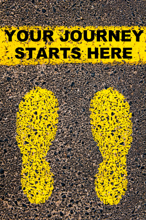 Conceptual image with yellow paint footsteps on the road in front of horizontal line over asphalt stone background. Message Your Journey Starts Here. Stock Photo
