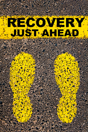 road to recovery: Conceptual image with yellow paint footsteps on the road in front of horizontal line over asphalt stone background. Message Recovery Just Ahead.