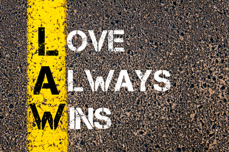 wins: Love Always Wins - LAW Concept. Conceptual image with yellow paint line on the road over asphalt stone background. Stock Photo