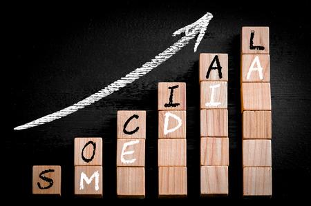 黒の背景に分離された木製つみきの棒グラフの上の矢印を昇順にメッセージ ソーシャル メディア。チョークは、黒板上に描画します。ビジネス コ