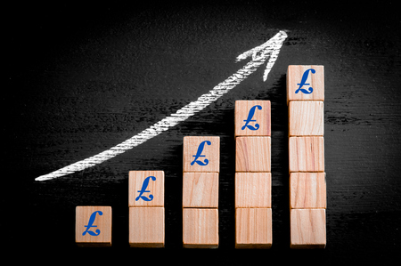 BRITISH POUND SIGN on ascending arrow above bar graph of Wooden small cubes isolated on black background. Chalk drawing on blackboard. Business Concept image. photo