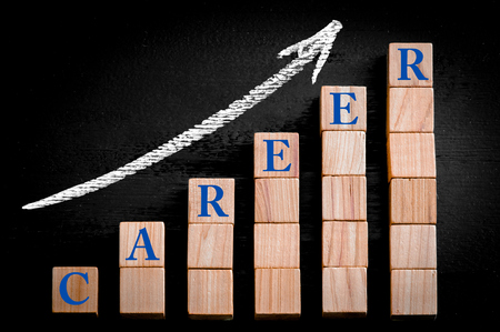 ascending: Word CAREER on ascending arrow above bar graph of Wooden small cubes isolated on black background. Chalk drawing on blackboard. Business Concept image. Stock Photo