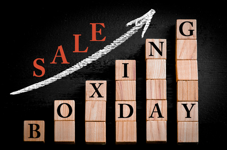 boxing day sale: Message BOXING DAY SALE on ascending arrow above bar graph of Wooden small cubes isolated on black background. Chalk drawing on blackboard. Business Concept image.