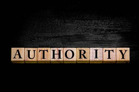 legitimate: Word AUTHORITY. Wooden small cubes with letters isolated on black background with copy space available. Concept image.