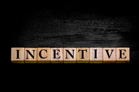 Word INCENTIVE. Wooden small cubes with letters isolated on black background with copy space available. Concept image.