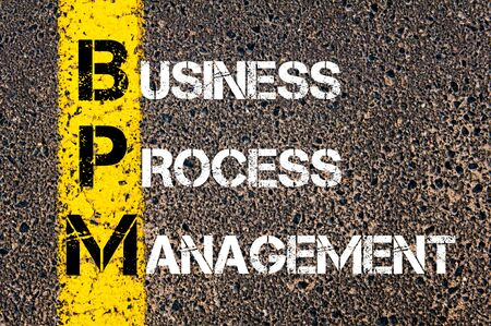 bpm: Acronym BPM - Business Process Management. Business Conceptual image with yellow paint line on the road over asphalt stone background. Stock Photo