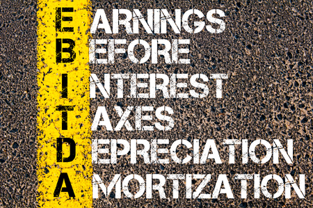 depreciation: Business Acronym EBITDA � Earnings before Interest, Taxes, Depreciation, and Amortization. Yellow paint line on the road against asphalt background. Conceptual image Stock Photo
