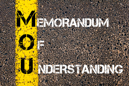 memorandum: Business Acronym MOU - Memorandum Of Understanding. Yellow paint line on the road against asphalt background. Conceptual image