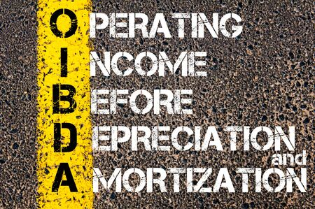 amortization: Business Acronym OIBDA - Operating Income Before Depreciation And Amortization. Yellow paint line on the road against asphalt background. Conceptual image
