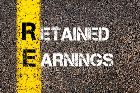 re: Business Acronym RE - Retained Earnings. Yellow paint line on the road against asphalt background. Conceptual image