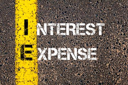 ie: Business Acronym IE - Interest expense. Yellow paint line on the road against asphalt background. Conceptual image