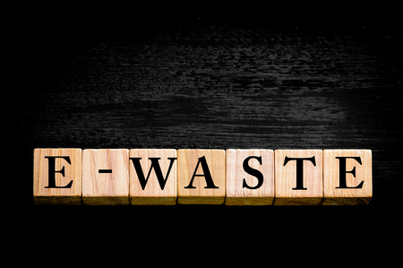 e waste: Word E-WASTE standing for ELECTRONIC WASTE. Wooden small cubes with letters isolated on black background with copy space available. Concept image. Stock Photo