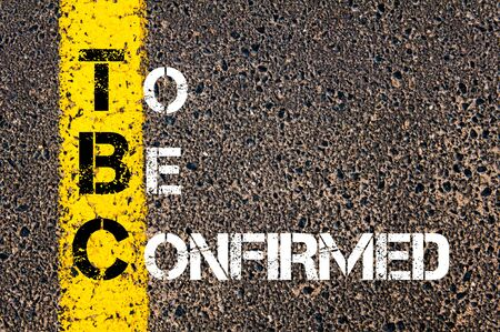 confirmed: Business Acronym TBC as To Be Confirmed. Yellow paint line on the road against asphalt background. Conceptual image