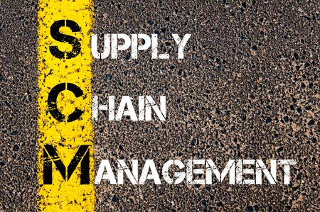 scm: Business Acronym SCM as Supply Chain Management. Yellow paint line on the road against asphalt background. Conceptual image