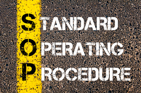 standards: Business Acronym SOP as Standard Operating Procedure. Yellow paint line on the road against asphalt background. Conceptual image
