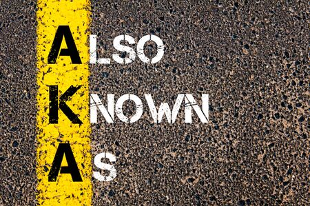 known: Acronym AKA as Also Known As. Yellow paint line on the road against asphalt background. Conceptual image