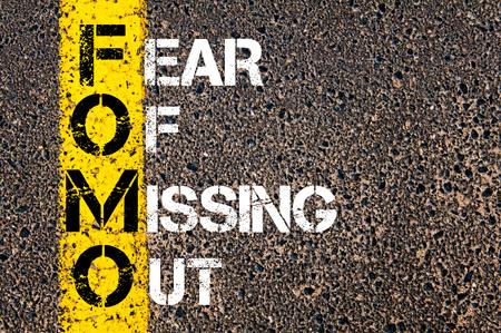 ソーシャル メディアの頭字語 FOMO 紛失の恐れとしてアウト。 アスファルトの背景に対して、道路上の黄色塗装ライン。概念図