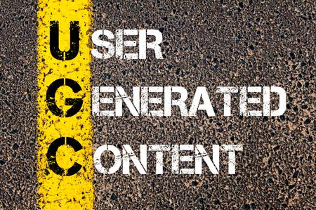ビジネス頭文字 UGC ユーザーとして生成されたコンテンツ。 アスファルトの背景に対して、道路上の黄色のペンキ ライン。概念図