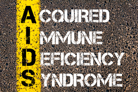 deficiency: Medical Acronym AIDS as Acquired Immune Deficiency Syndrome. Yellow paint line on the road against asphalt background. Conceptual image Stock Photo