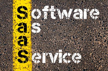 ソフトウェアとしてのサービスとしてビジネスの頭字語 SaaS。 アスファルトの背景に対して、道路上の黄色塗装ライン。概念図