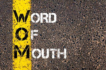 word of mouth: Acronym WOM as Word Of Mouth. Yellow paint line on the road against asphalt background. Conceptual image