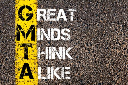 alike: Business Acronym GMTA as Great Minds Think Alike. Yellow paint line on the road against asphalt background. Conceptual image