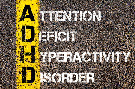 hyperactivity: Medical Acronym ADHD as ATTENTION DEFICIT HYPERACTIVITY DISORDER. Yellow paint line on the road against asphalt background. Conceptual image