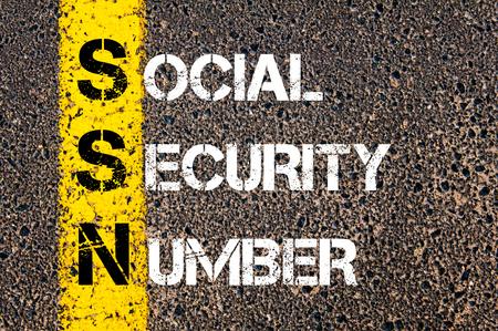 seguridad social: Acrónimo SSN como número de Seguro Social. Línea de pintura amarilla en el camino contra el fondo de asfalto. Imagen conceptual