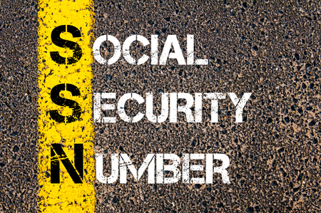 security symbol: Acronym SSN as Social Security Number. Yellow paint line on the road against asphalt background. Conceptual image