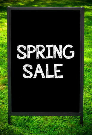 sidewalk sale: SPRING SALE  message on sidewalk blackboard sign against green grass background. Copy Space available. Concept image Stock Photo