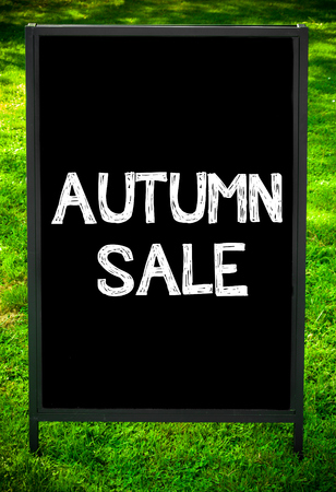 sidewalk sale: AUTUMN SALE  message on sidewalk blackboard sign against green grass background. Copy Space available. Concept image