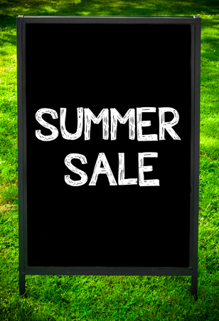 sidewalk sale: SUMMER SALE  message on sidewalk blackboard sign against green grass background. Copy Space available. Concept image Stock Photo