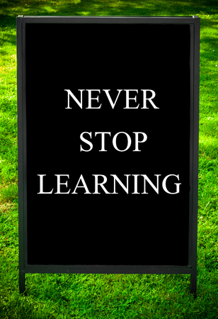 NEVER STOP LEARNING  message on sidewalk blackboard sign against green grass background. Copy Space available. Concept image photo