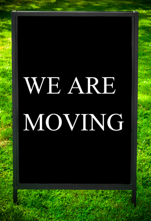 WE ARE MOVING message on sidewalk blackboard sign against green grass background. Copy Space available. Concept image
