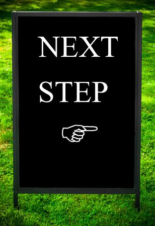 the next step: Messaggio passo successivo e la mano che punta a destra sul marciapiede lavagna segno contro sfondo verde erba. Copia di spazio disponibile. Concetto di immagine
